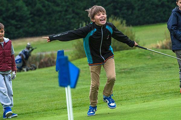 junior golf boy happy